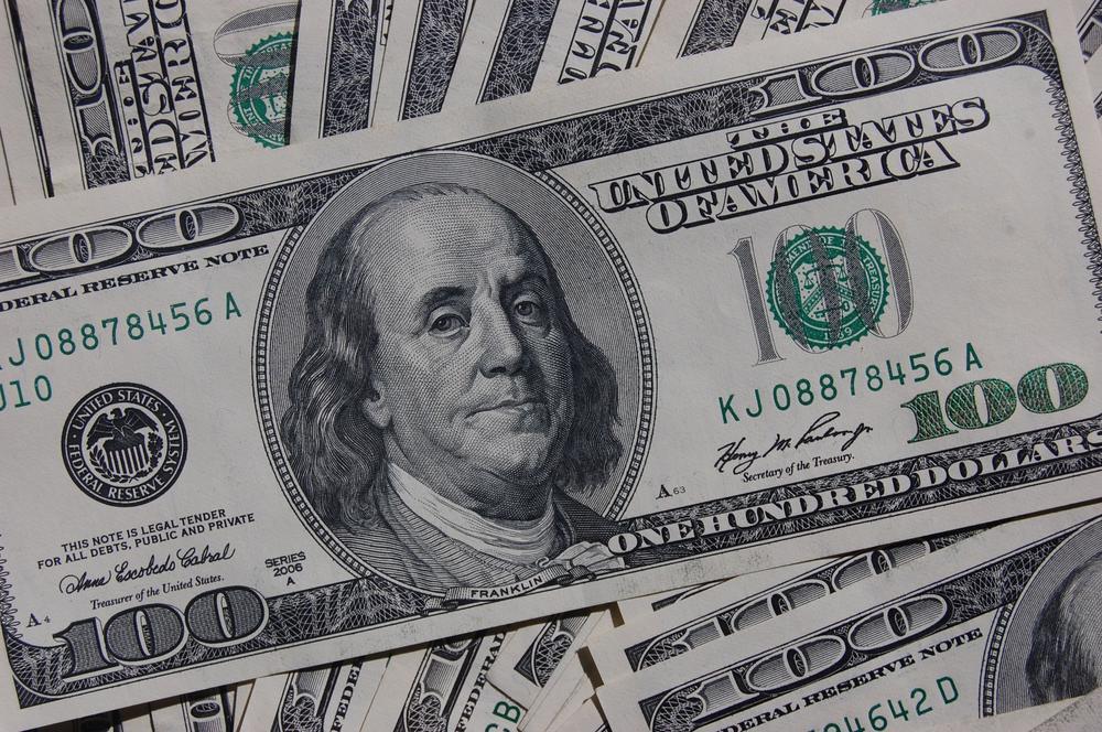 Im Vordergrund eine 100-Dollar-Geldnote, die auf weitern Geldscheinen liegt.