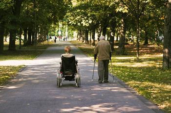 Eine Rentnerin im Rollstuhl und ein Rentner am Stock beim Spazieren durch einen Park.