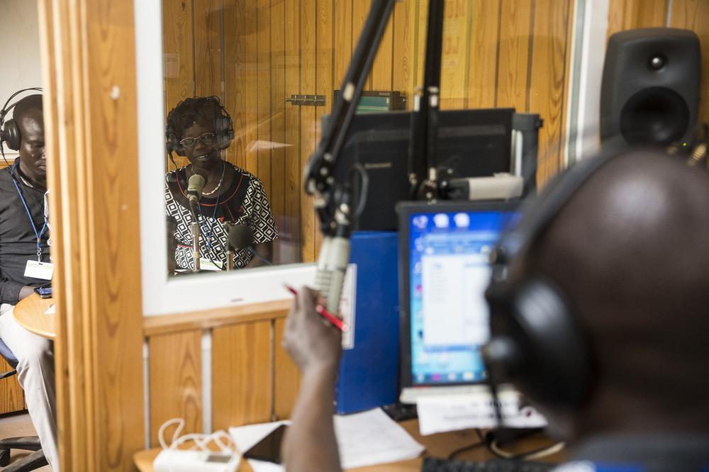 Radiostudio mit Holzpanelen an den Wänden. Vor den Mikrophonen sitzen ein Mann und eine Frau, die von einem Toningenieur außerhalb des Studios beobachtet werden.