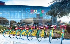 Die gläserne Front der Google-Zentrale mit mit dem Namensschriftzug und gelben Fahrrädert im Vordergrund.