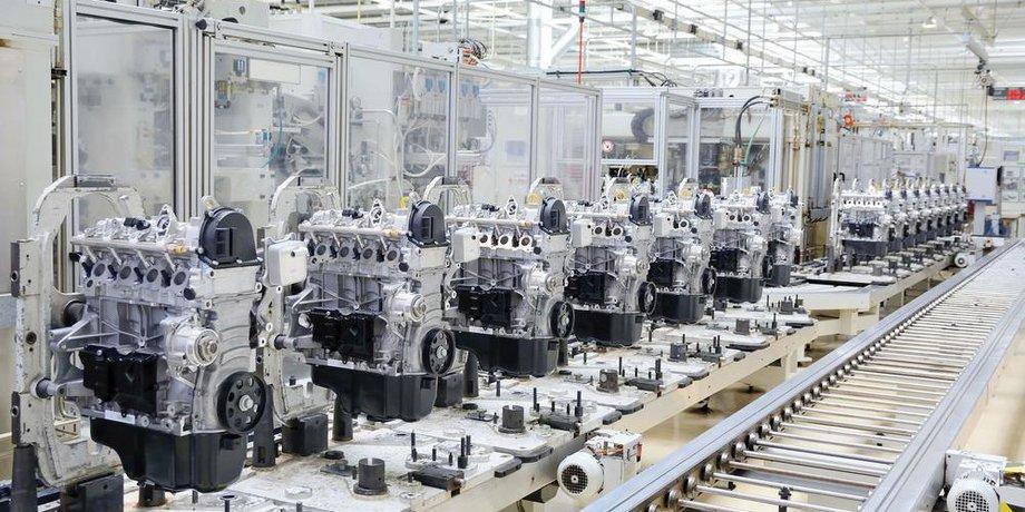Fließband mit Motoren in einer menschenleeren Fabrikhalle, alles in einem silbrigen Ton gehalten.