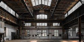Eine leere Fabrikhalle mit einem Glasdach in der Mitte.