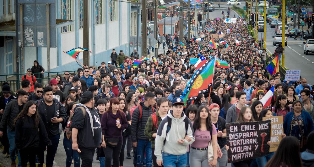 Demonstrationszug, der sich eine lange gerade Sraße entlangstreckt.