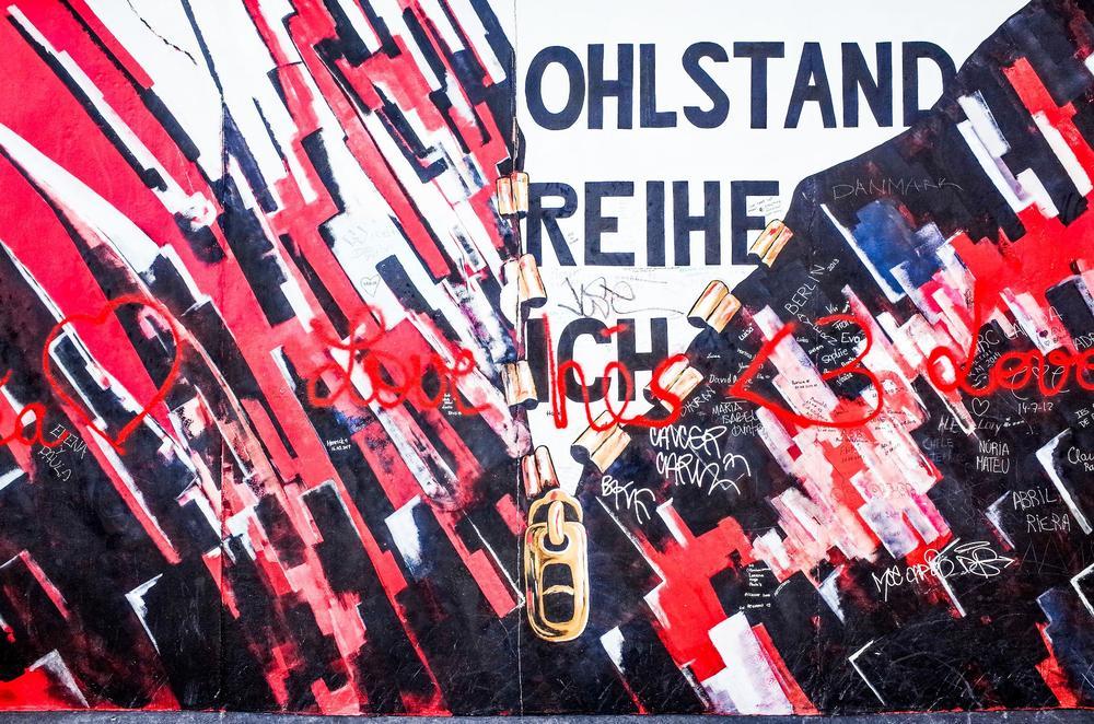 Gemälde auf einem Mauerstück. Ein Reißverschluss wird heruntergezogen, was die Öffnung der Mauer symbolisiert.