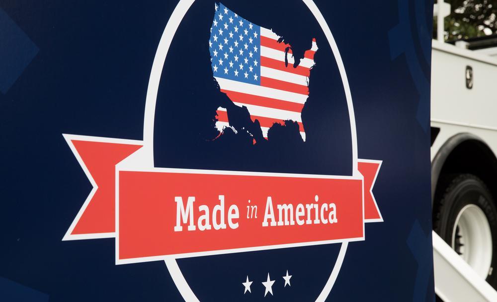 """Schild, auf dem oben eine US-Flagge in Form der USA abgebildet ist und darunter steht """"Made in America"""""""