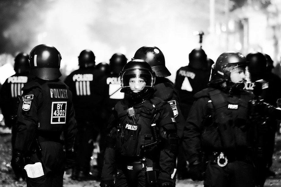 Polizisten stehen nebeneinander in Kampfkleidung auf einer Straße. Im Hintergrund scheint Rauch aufzusteigen.
