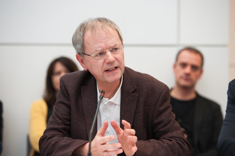 Christoph Butterwegge sitzt an einem Tisch und spricht in ein Mikrophon vor ihm. Im Hintergrund sitzen zwei Zuhörer rechts und links von ihm.