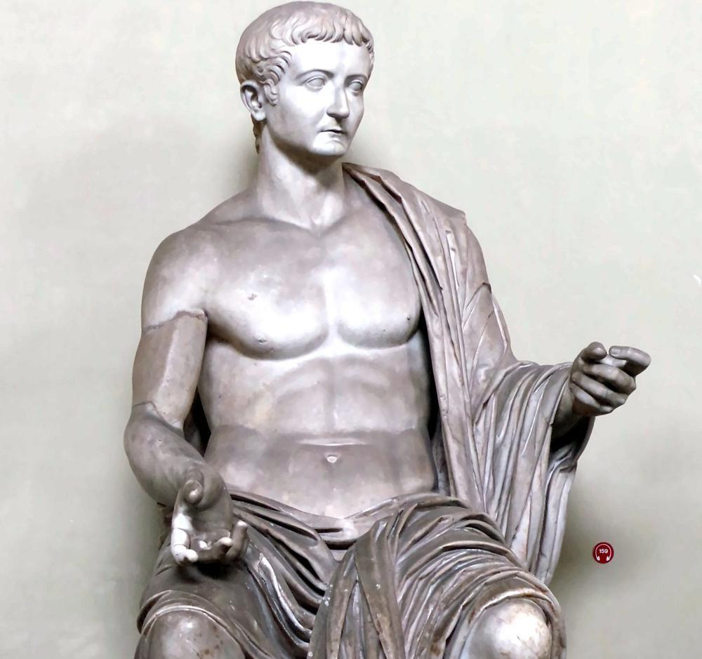 Skulptur aus Marmor, die einen sitzenden Mann mit Toga zeigt.