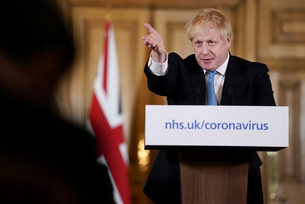 Boris Johnson steht hinter einem Rednerpult und weist mit der rechten Hand ins Publikum.