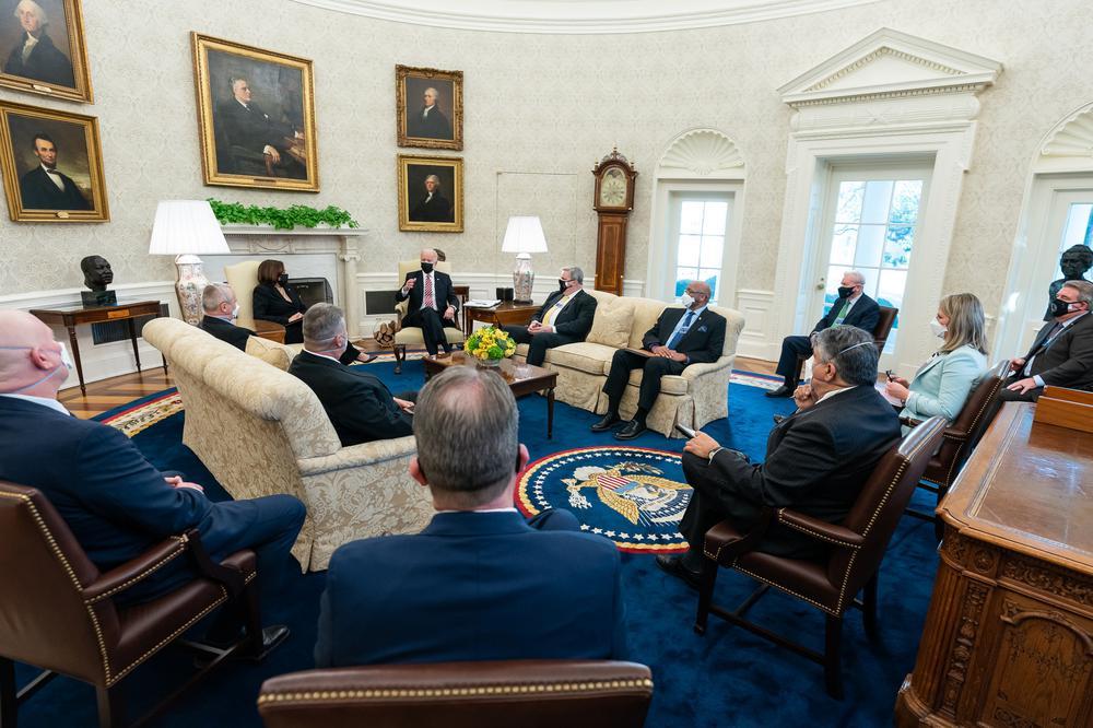Im Oval Office im Weißen Haus sitzen Kamala Harris und Joe Biden einer Gruppe von Männern und einer Frau auf zwei Sofas und mehreren Stühlen gegenüber.