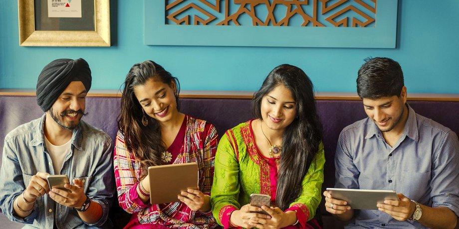 Zwei Männer und zwei Frauen in indischen Gewändern sitzen auf einer Bank und blicken entweder auf ein Smartphone oder ein Tablet.