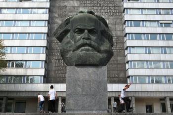 Karl-Marx-Statue in Chemnitz vor einem Plattenbau.
