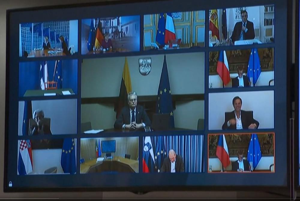 Großer Bildschirm mit vielen kleinen Bildchen von Politikern während einer Videokonferenz.