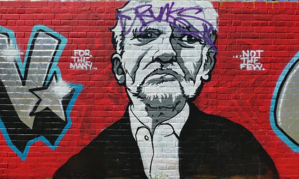 Graffiti von Jeremy Corbyn auf roter Ziegelsteinwand.