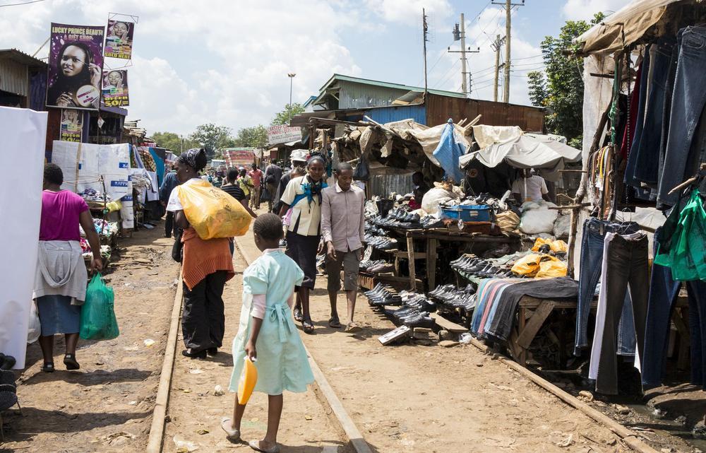 Eine Eisenbahnstrecke führt mitten durch das Slum Kibera in Nairobi, Kenia. Menschen flanieren dort zwischen Marktständen für Kleidung rechts und links der Gleise.