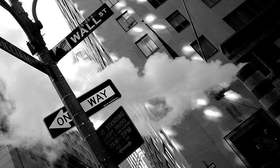 Schwarzweißbild vom Straßenschild, auf dem Wall Street steht, schräg aufgenommen, so dass es fast aus dem Bild kippt.