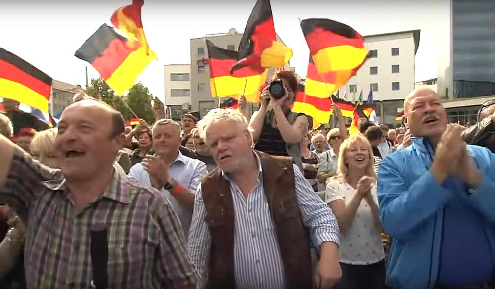 Menschen in der Zuschauermenge jubeln und wedeln mit Deutschland-Flaggen