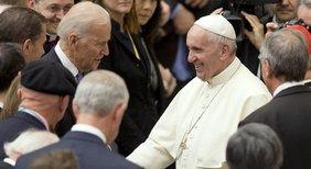 Joe Biden und Papst Franziskus reichen sich die Hände, umgeben von mehreren Leuten.