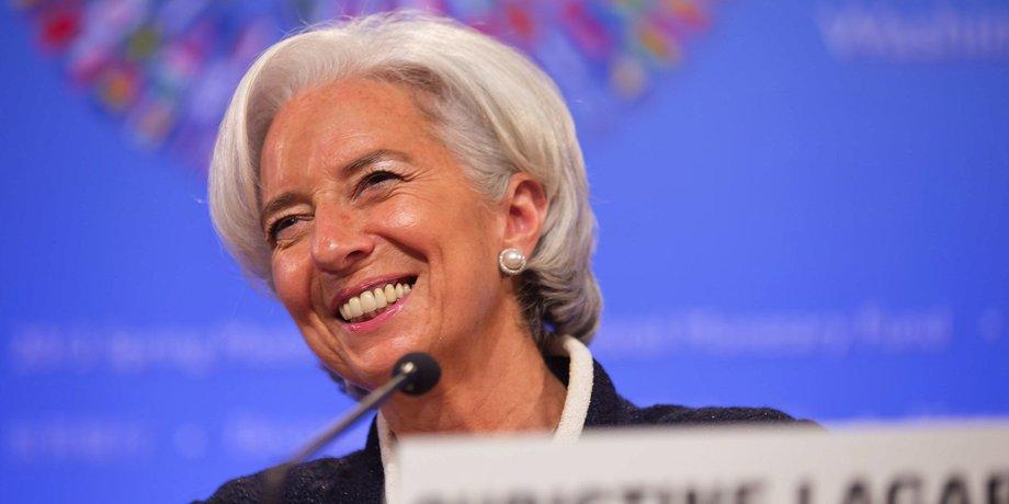 Christine Lagarde lächeln hinter einem Tisch mit Mikro.