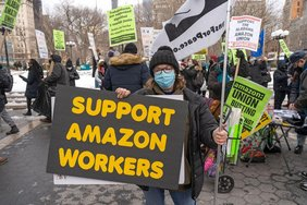 Arbeiterinnen und Arbeiter halten Protestschilder gegen Amazon hoch und fordern Unterstützung bei der Gewerkschaftsarbeit.