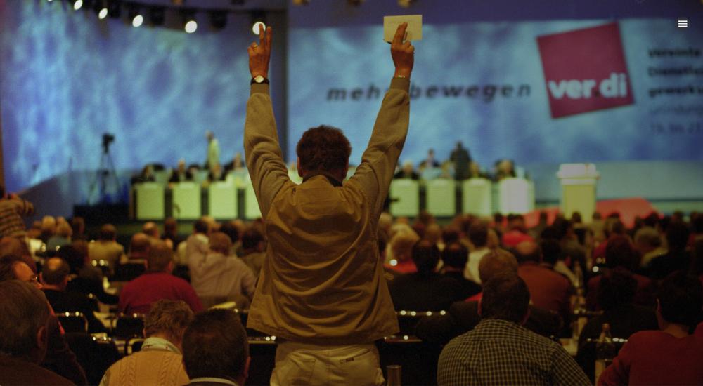 Gründungskongress von Verdi. Blick aus dem Publikum auf die Bühne, im Vordergrund ein Mann von hinten, der eine gelbe Karte hochhält.