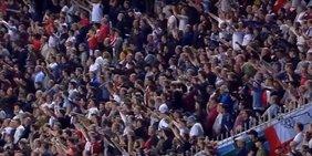 Fußballfans in einem vollbesetzten Stadion zeigen den Hitlergruß.