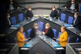 Angela Merkel spricht vor dem Bundestag. In der linken Bildhälfte spiegelt sich die Kanzlerin.