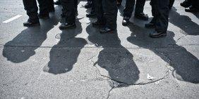 Schatten von Polizisten auf Demonstration