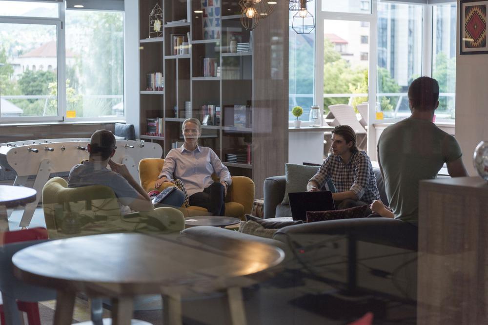 Junge Frauen und Männer sitzen in einem Großraumbüro auf Sesseln in der Mitte. Im Hintergrund ist eine große Fensterfront, vor der ein Tischfußball und Schreibtische zu erkennen sind.