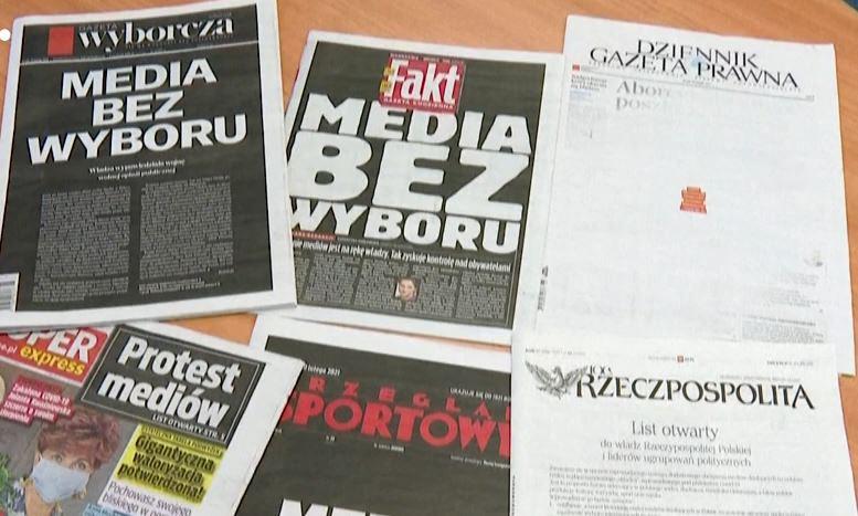 Zeitungen mit polnischen Schlagzeilen auf schwarzem Grund liegen auf einem Tisch.
