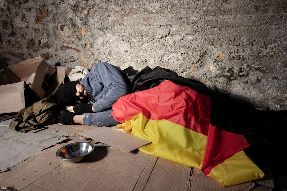Ein Obadachloser liegt auf einem Pappkarton unter einer Deutschlandflagge.