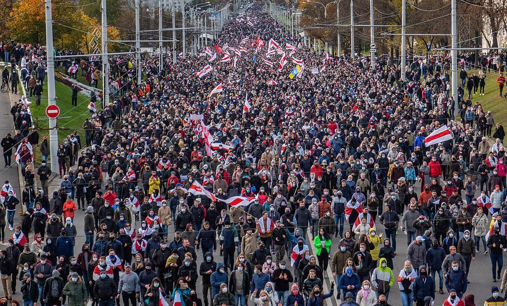 Eine riesige Gruppe Menschen zieht bei einer Demonstration eine lange Straße entlang auf die Kamera zu.