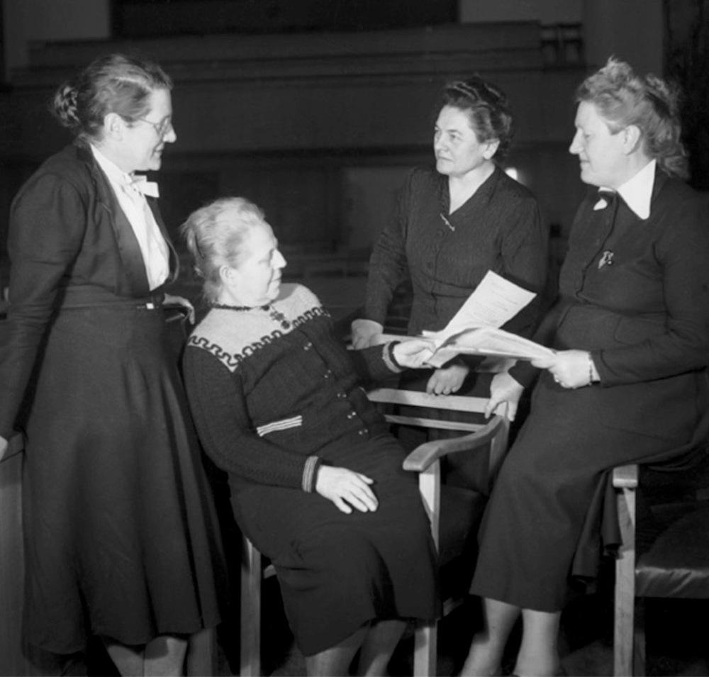 Vier Frauen auf einem Schwarzweißbild, eines sitzt auf einem Stuhl, die anderen stehen um sie herum. Alle tragen dunkle hochgeschlosse Kleider.