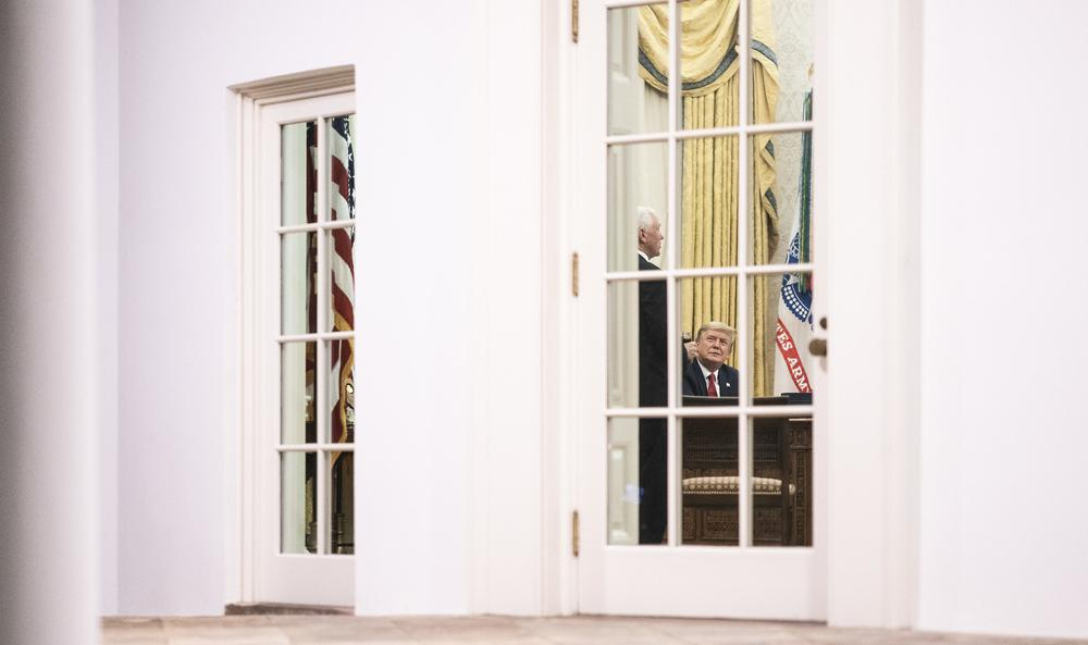 Das Oval Office von außen aufgenommen. Durch die Scheibe ist Donald Trump am Schreibtisch zu sehen, daneben steht, halb nur zu sehen, seine Vize Mike Pence.