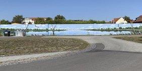 Eine Straße macht einen Bogen und führt auf eine Wand zu, die mit einem See und umliegenden Bäumen bemalt ist.