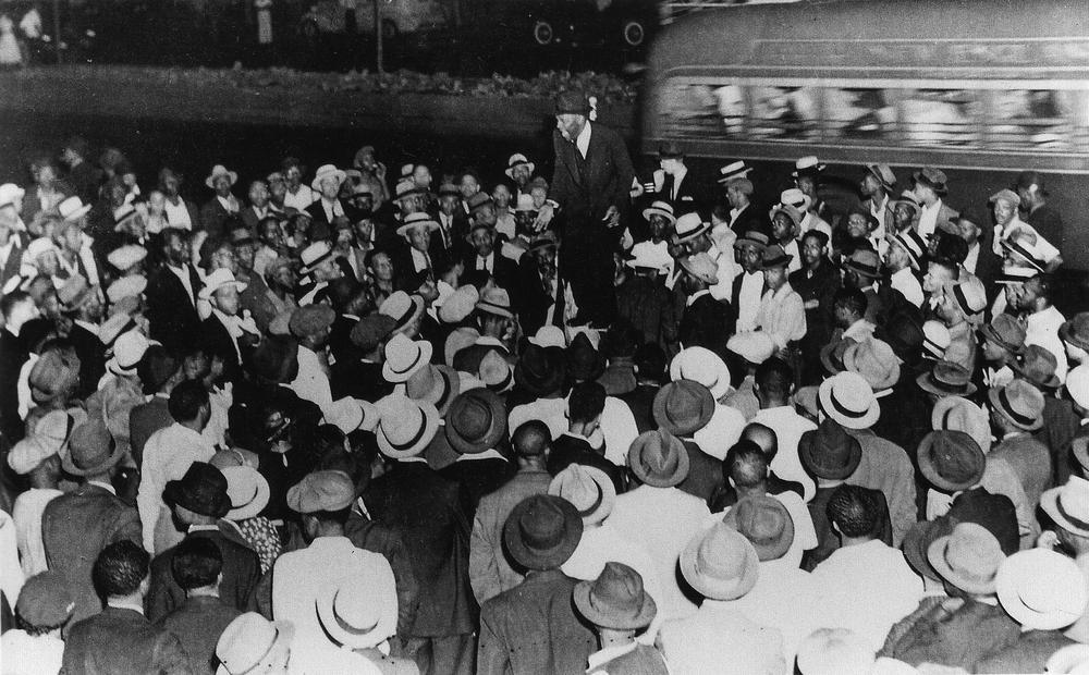 Schwarzweiß-Bild von einem Redner auf einer Seifenkiste, umgeben von einer Menschenmenge, die ihm zuhört.