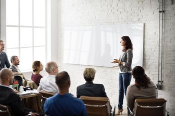 Schulung mit einer Ausbilderin vor einer Gruppe von Menschen