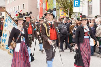 Umzug in bayerischen Trachten mit weißblauer Fahne.