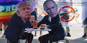 Zwei Männer mit Masken, eine mit Putin-Gesicht, eine mit Trump-Gesicht, sitzen sich gegenüber und halten jeweils eine Hand über einen roten Knopf.