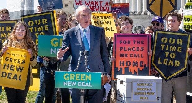 Ein Mann steht vor einer Gruppe von Menschen, die Schilder hochhalten, auf denen ein Green New Deal gefordert wird. Er spricht in ein Mikrofon.