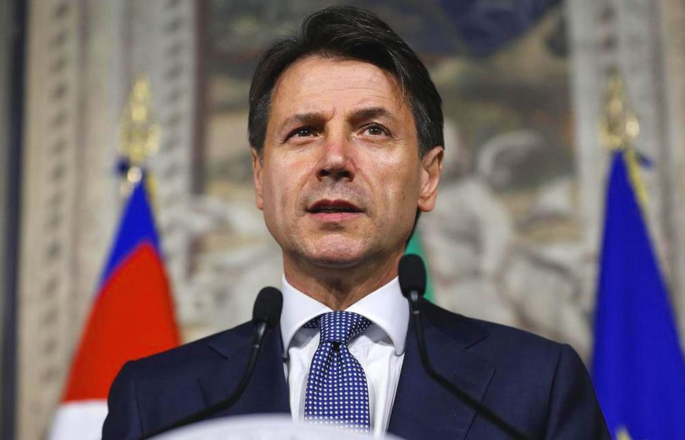 Giuseppe Conte hinter zwei Mikrophonen an einem Stehpult.