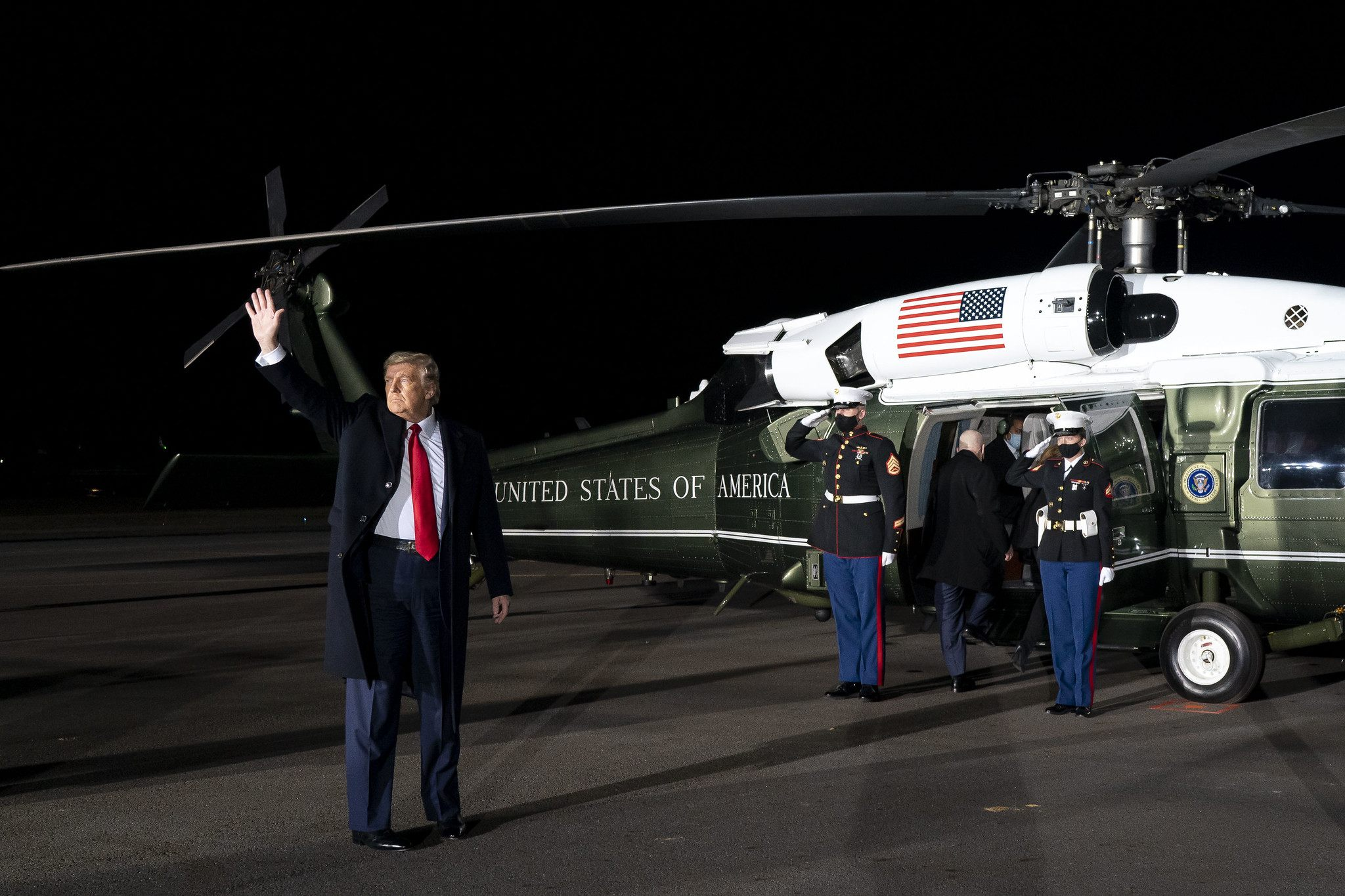 Donald Trump winkt, kurz bevor er in den Hubschrauber einsteigen wird, der einige Meter hinter ihm steht. Es ist Nacht.