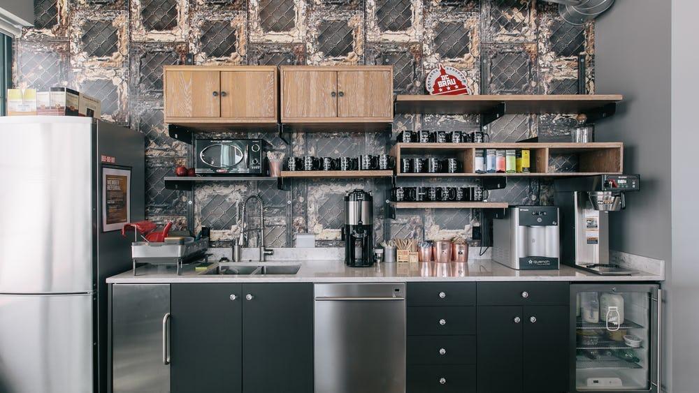 Teeküche in Edelstahl mit Espresso-Maschine, Kaffeemaschine, Kochplatten und einen Kühlschrank.