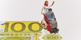 Figur im Rollstuhl mit Pflegerin und Geldschein