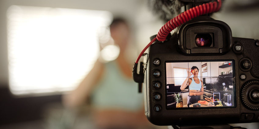 Durch eine Fotokamera wird eine Frau aufgenommen, die in der Küche in knapper Sportbekleidung steht und etwas zubereitet.