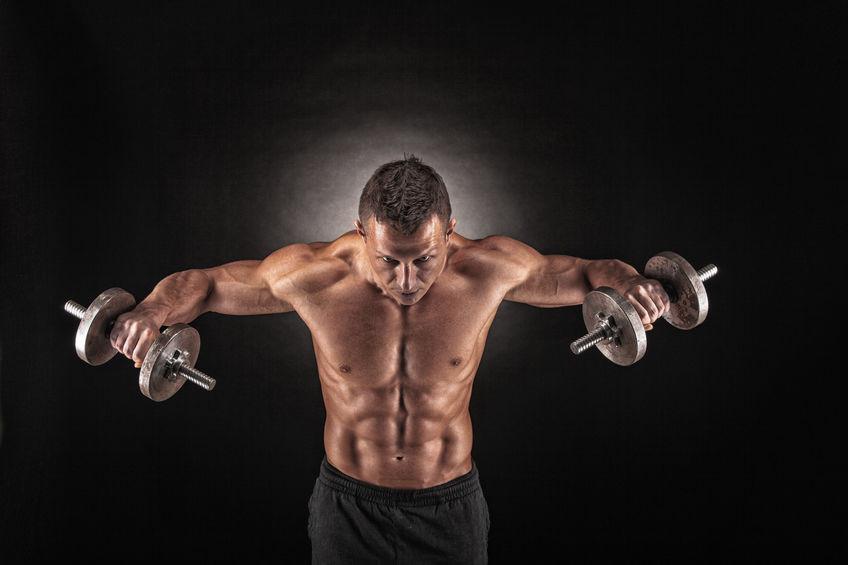 Ein Bodybuilder stemmt mit jeder Hand eine Kurzhantel hoch, was seinen muskulösen Körper unterstreicht.