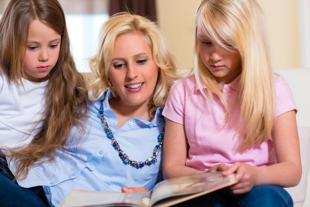 Eine Mutter liest zwei Mädchen aus einem Buch vor.