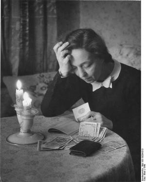 Eine Frau schaut ihr Haushaltsbuch durch und zählt das verbliebene Geld auf dem Tisch 1948
