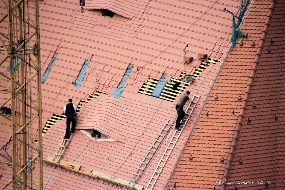 Dachdecker auf einem hohen Kirchendach