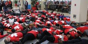 Menschen in roten Sweatshirts liegen auf dem Boden in der Flughafen-Halle.